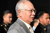 Former Malaysian prime minister Najib Razak is escorted by police after being charged in Kuala Lumpur