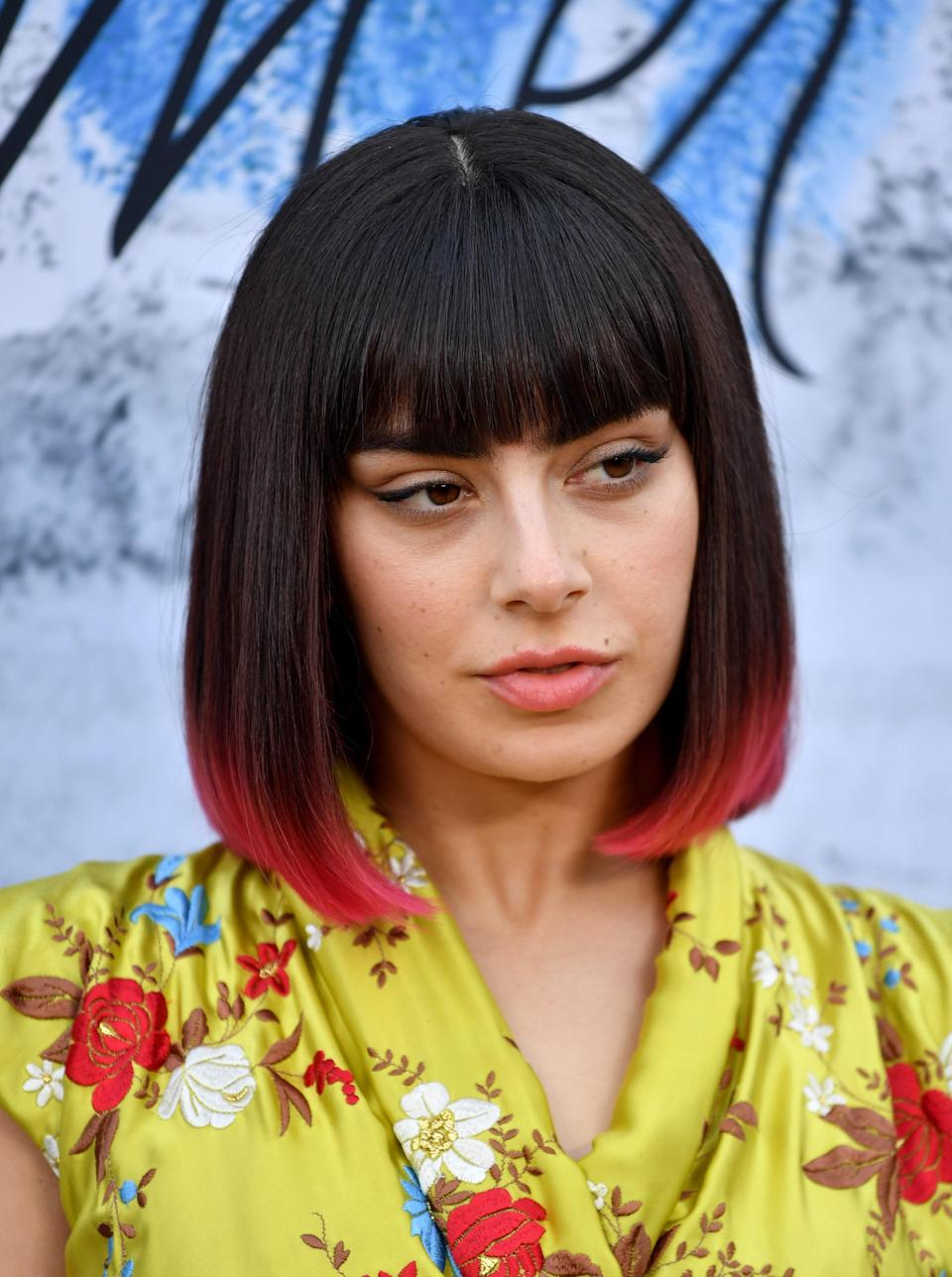 Charli XCX makes a sharp bob her own with bright pink tips and heavy bangs.