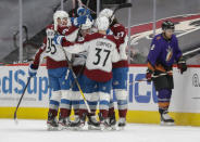 Colorado Avalanche's Andre Burakovsky (95), J.T. Compher (37) and Ryan Graves (27) mob Jacob MacDonald, center, after a goal against the Arizona Coyotes during the second period of an NHL hockey game Saturday, Feb. 27, 2021, in Glendale, Ariz. Coyotes' Nick Schmaltz skates in the background. (AP Photo/Darryl Webb)