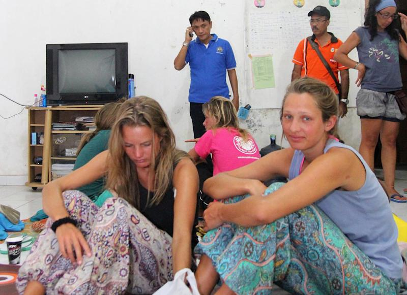 Survivors rescued after a tourist boat sank rest at a house near to the Indonesian town of Bima on August 17, 2014
