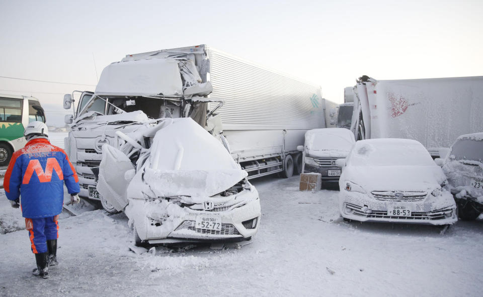 Damaged cars are covered with snow after a multiple accident on the Tohoku Expressway in Osaki city, Miyagi prefecture, northern Japan, Tuesday, Jan. 19. 2021. (Yusuke Ogata/Kyodo News via AP)