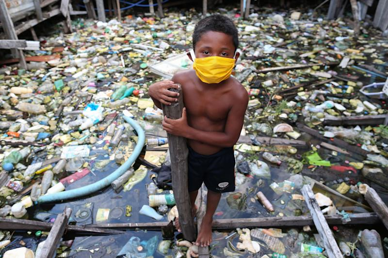 A boy from the Educandos riverside community wears a face mask during the COVID-19 coronavirus pandemic in Manaus, the Amazon on May 26, 2020. - The Nossa Senhora Perpetuo Socorro church has been handing out masks to impoverished members of its community to assist in the fight against the spread of the novel coronavirus. (Photo by MICHAEL DANTAS / AFP) (Photo by MICHAEL DANTAS/AFP via Getty Images)