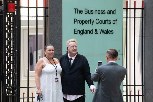 John Lydon, centre, poses for a photo outside the Rolls Building at the High Court