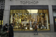 People wearing face masks to try to curb the spread of coronavirus walk past the temporarily closed Topshop flagship store on Oxford Street, during England's second coronavirus lockdown, in London, Monday, Nov. 30, 2020. Arcadia Group, the retail empire of tycoon Philip Green, which owns well-known British fashion chains like Topshop and employs around 15,000 people, appears to be on the brink of collapse following the economic shock of the coronavirus pandemic. (AP Photo/Matt Dunham)