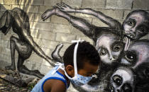 """A boy wearing a mask as a precaution against the spread of the new coronavirus plays in front of a mural by artist Yulier P. titled """"Marcha Hacia la Oscuridad,"""" or Move Toward Darkness, in the patio of a home in Havana, Cuba, Friday, April 10, 2020. Yulier P. said his latest murals show humanity's powerlessness against the COVID-19 disease. (AP Photo/Ramon Espinosa)"""