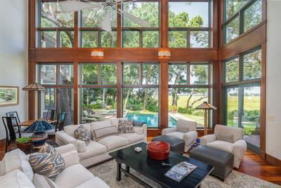 In the grand salon, soaring, 20-ft walls of windows reveal an expanse of peaceful marshes to the east and deep-water views to the west. SavannahLuxuryAuction.com