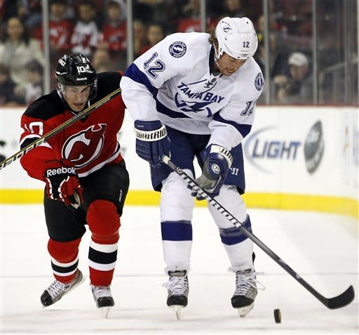 Tampa Bay Lightning's Ryan Malone (12) and New Jersey Devils' Peter Harrold (10) compete for the puck in the first period of an NHL hockey game, Thursday, March 29, 2012, in Newark, N.J. (AP Photo/Julio Cortez)
