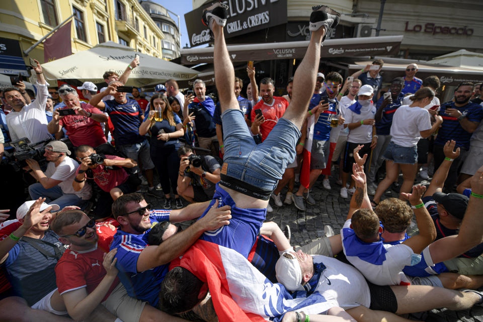 FILE - In this June 28, 2021, file photo, France's fans cheer prior to the Euro 2020 soccer championship round of 16 match between France and Switzerland in the old city district of Bucharest, Romania. Countries across Europe are scrambling to accelerate coronavirus vaccinations to outpace the spread of the delta variant in a high-stakes race to prevent hospital wards from filling up again with patients fighting for their lives. (AP Photo/Andreea Alexandru, File)