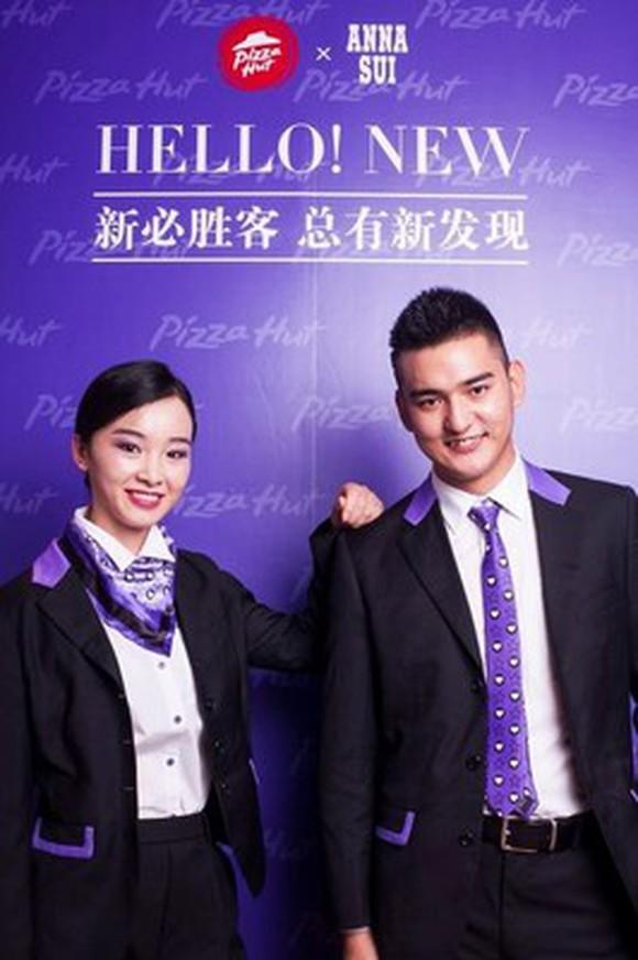 Two Pizza Hut employees wearing the new formal wear by Anna Sui. Both are wearing dark black suits with purple accents.