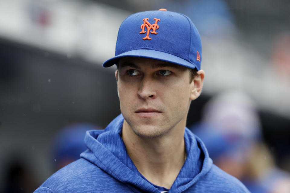 New York Mets pitcher Jacob deGrom watches from the dugout in the seventh inning of a baseball game against the Philadelphia Phillies, Sunday, Sept. 9, 2018, in New York. He was scheduled to pitch the game but was scratched beforehand. (AP Photo/Mark Lennihan)