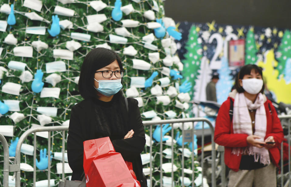 Masked women stand in front of a coronavirus-themed Christmas tree decorated with masks and rubber gloves in Hanoi, Vietnam, Thursday, Dec. 24, 2020. (AP Photo/Hau Dinh)