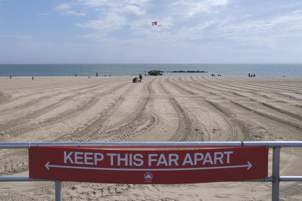 FILE - In this April 12, 2020, file photo, a sign on the Coney Island boardwalk reminds people to keep their distance in New York. From Cape Cod to California, festivals are being canceled, businesses in tourist havens are looking at empty reservation books, and people who have been cooped up through a dismal spring are worrying summer will bring just more of the same. (AP Photo/Seth Wenig, File)
