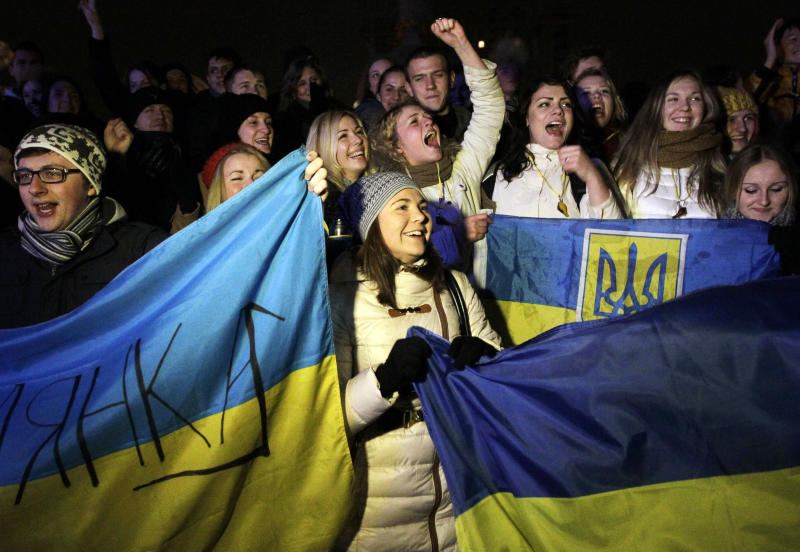 Activists wave Ukrainian flags during a night rally in support of Ukraine's integration with the European Union in the center of Kiev, Ukraine, Friday, Nov. 21, 2013. Ukraine's president-controlled parliament on Thursday failed to pass any of a flurry of proposed bills allowing the release of jailed former premier Yulia Tymoshneko, dealing a harsh blow to this ex-Soviet republic's chances of integration with the European Union. (AP Photo/Sergei Chuzavkov)