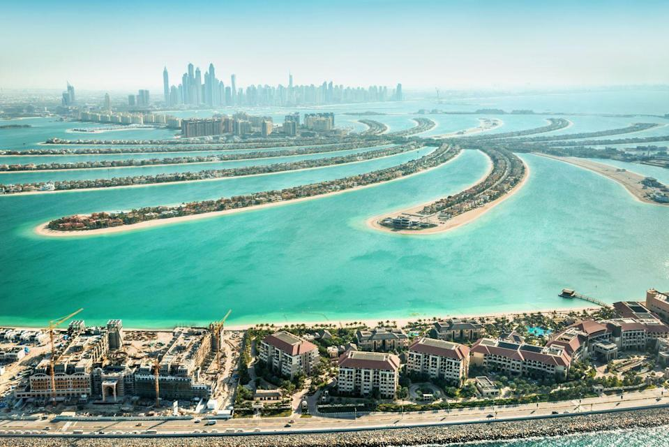 "<p>You won't find the skyline of a major city looming over any other of these beaches, that's for sure. Conceived by developers, <a href=""https://www.britannica.com/topic/Palm-Jumeirah"" rel=""nofollow noopener"" target=""_blank"" data-ylk=""slk:Palm Jumeirah,"" class=""link rapid-noclick-resp"">Palm Jumeirah,</a> which is shaped like a palm, began construction in 2001. With the shadows of Dubai in the distance, this is a luxury resort riposte to the desert heat.</p>"