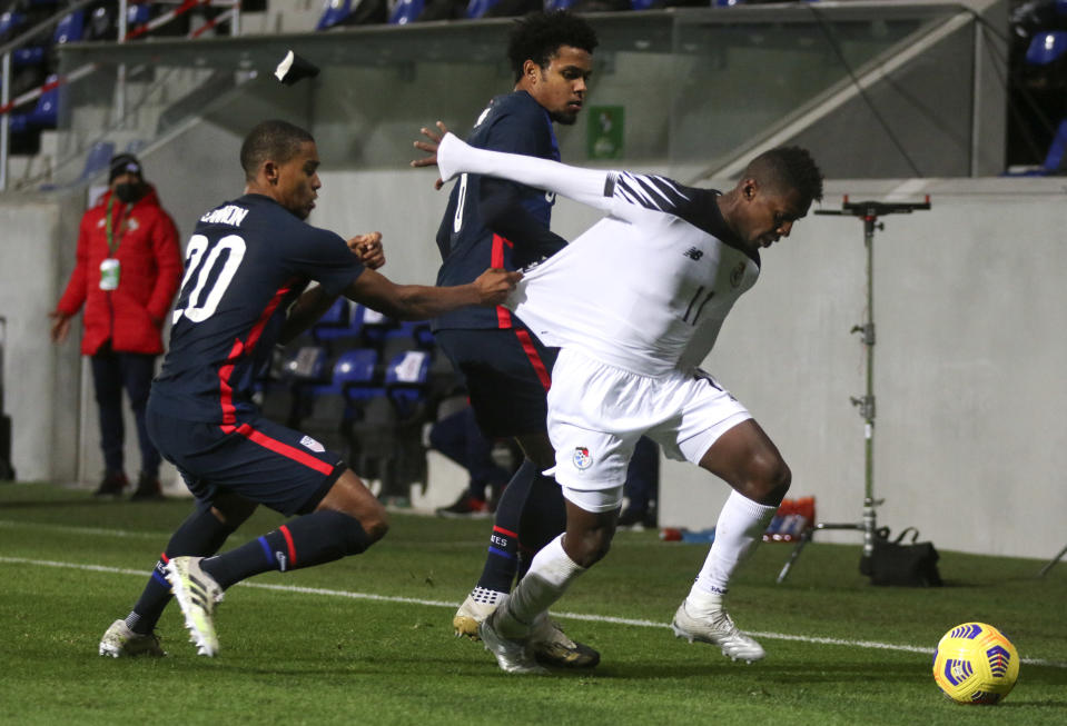 United States' Reggie Cannon, left, pulls at the shirt of Panama's Armando Cooper during the international friendly soccer match between the USA and Panama at the SC Wiener Neustadt stadium in Wiener Neustadt, Austria, Monday, Nov. 16, 2020. (AP Photo/Ronald Zak)