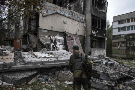 A pro-Russian rebel stands in front of a building that was destroyed in the recent shelling, in the town of Yasinovataya