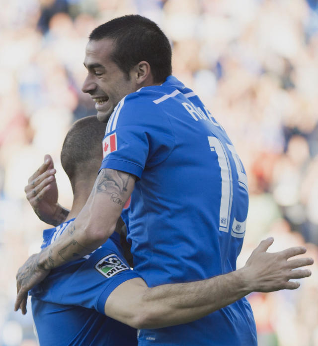Montreal Impact's Andres Romero, right, celebrates with teammate Marco Di Vaio after scoring against New England Revolution during first half MLS soccer action in Montreal, Saturday, May 31, 2014. (AP Photo/The Canadian Press, Graham Hughes)