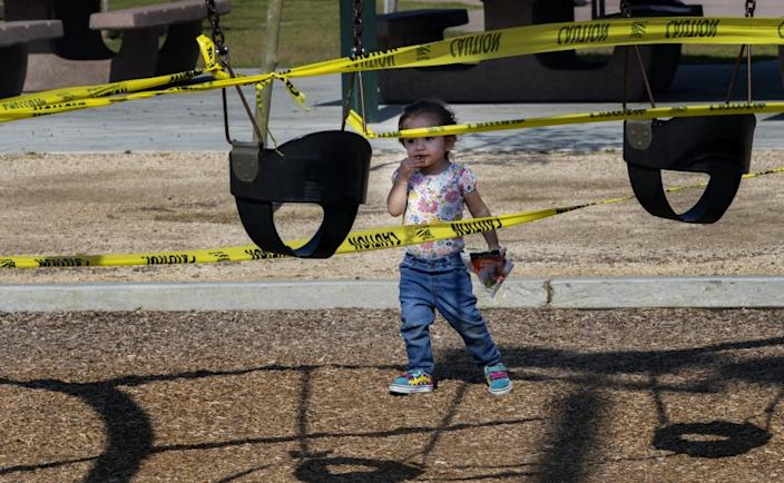 RIVERSIDE, CALIFORNIA - APRIL 3, 2020: Adeline Hernandez, 2, of Riverside seems perplexed by the yellow caution tape as she approaches the closed off swing sets during the coronavirus pandemic at Ryan Bonaminio Park on April 3, 2020 in Riverside, California. She was visiting the park with her dad Erick Hernandez. All the playground equipment and drinking fountains are closed off with yellow caution tape.(Gina Ferazzi/Los Angeles Times)