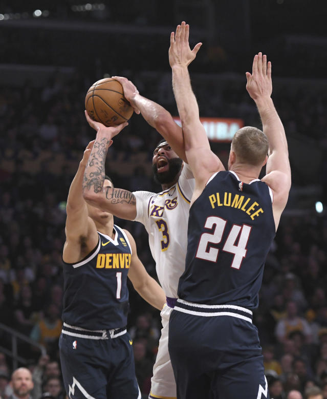 Los Angeles Lakers forward Anthony Davis is fouled as he shoots between Denver Nuggets forward Michael Porter Jr., left, and center Mason Plumlee during the first half of an NBA basketball game Sunday, Dec. 22, 2019, in Los Angeles. (AP Photo/Michael Owen Baker)
