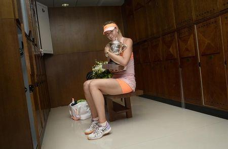 Maria Sharapova of Russia poses with her trophy in the dressing room after winning the women's singles final match against Simona Halep of Romania during the French Open tennis tournament at the Roland Garros stadium in Paris