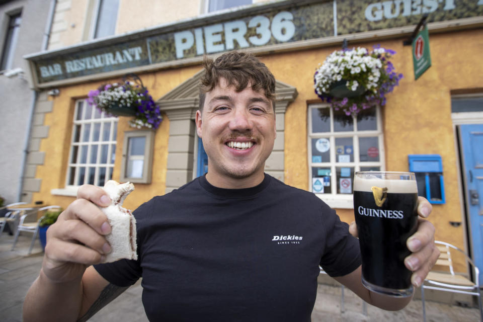 Jordan Leckey holding a celebrity jam sandwich and pint of Guinness outside Pier 36 at Donaghadee Harbour in Northern Ireland after his record swim (Liam McBurney/PA)