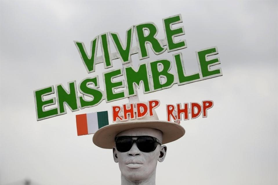 "A supporter with a painted face wears a hat with a slogan in relief during a campaign rally for the October 31, 2020 presidential election in Abidjan, Ivory Coast, October 17, 2020. The slogan reads ""Live together RHDP, RHDP""."