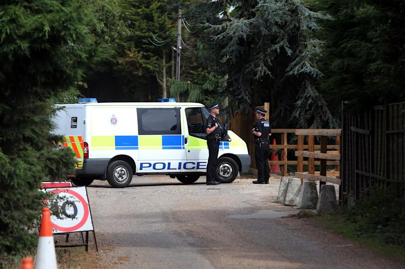 Police stand at Earls Hall Farm in St Osyth, southern England where a lion was apparently seen Monday Aug. 27, 2012. Outside the idyllic English village of St. Osyth, police are hunting a lion. A small army of officers and tranquilizer-toting zoo experts, along with a pair of heat-seeking helicopters, are spending their Monday combing the woods, ponds, and farmland around the coastal community after a resident spotted what was believed to be a lion lounging in a field of grass. Where such a beast may have come from is anyone's guess; the local zoo says its animals are accounted for, and police have said a local circus isn't missing any either. (AP Photo/Steve Parsons/PA Wire)  UNITED KINGDOM OUT