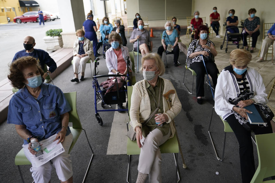 Residents wait to be cleared after receiving the Pfizer-BioNTech COVID-19 vaccine at the The Palace assisted living facility, Tuesday, Jan. 12, 2021, in Coral Gables, Fla. (AP Photo/Lynne Sladky)