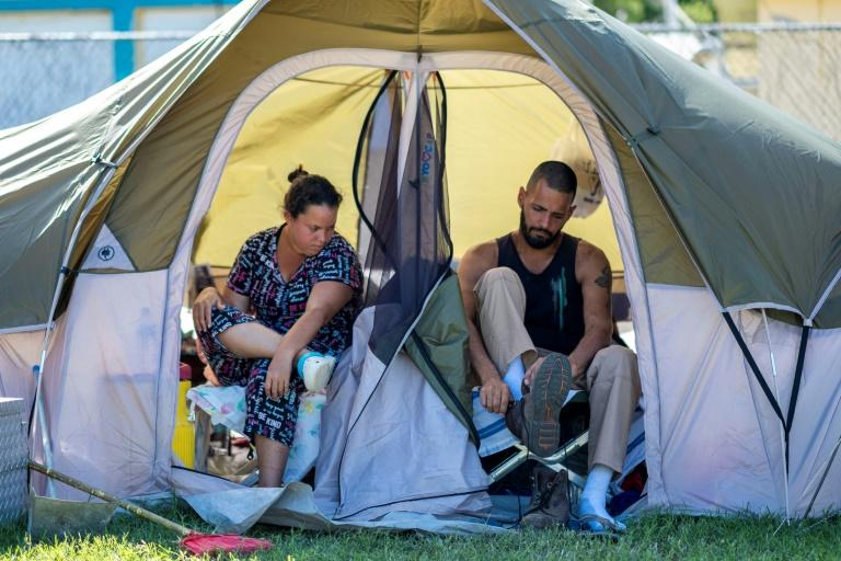 Juan Santiago gets ready for work as his wife, Solmely Velazquez looks on in their tent in a baseball field in Guanica, Puerto Rico on January 15, 2020, after a powerful earthquake hit the island (AFP Photo/Ricardo ARDUENGO)