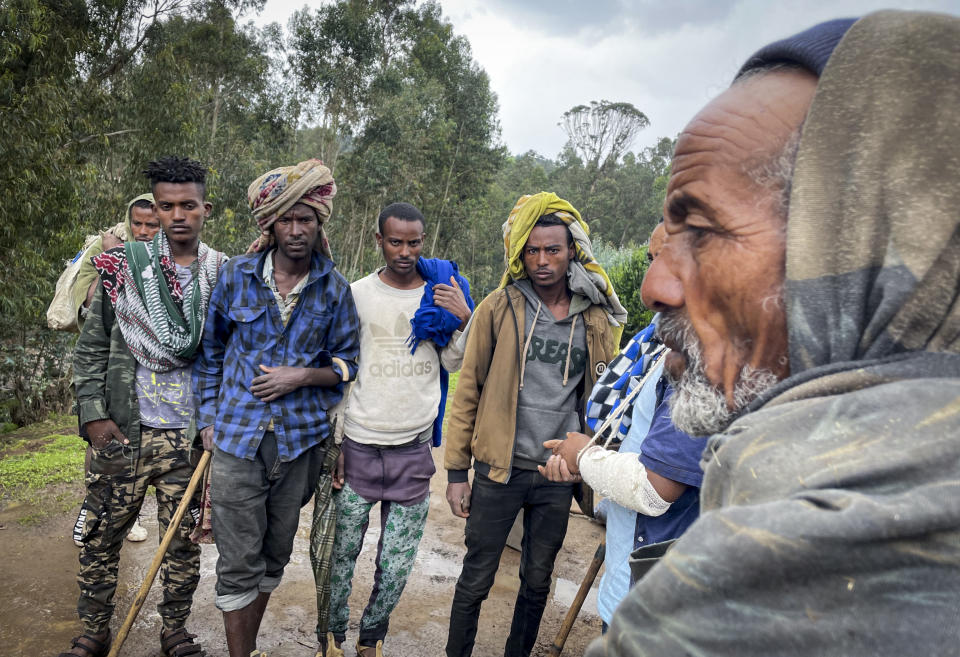 """Men gather to speak to a militia fighter Kibret Bidere, with an injured arm, 2nd right, near the village of Chenna Teklehaymanot, in the Amhara region of northern Ethiopia Thursday, Sept. 9, 2021. At the scene of one of the deadliest battles of Ethiopia's 10-month Tigray conflict, witness accounts reflected the blurring line between combatant and civilian after the federal government urged all capable citizens to stop Tigray forces """"once and for all."""" (AP Photo)"""