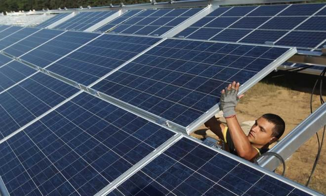 A worker installs solar panels containing photovoltaic cells at the Solarpark Eggersdorf solar park near Muencheberg, Germany.