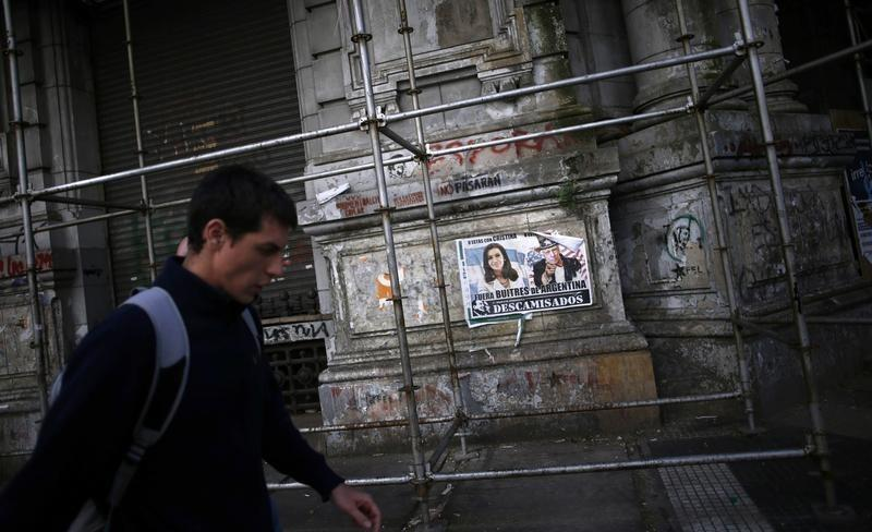 A man walks past a poster with pictures of Argentina's President Fernandez de Kirchner and U.S. for the Southern District of New York Judge Griesa, depicted as Uncle Sam, near the Argentine Congress in Buenos Aires