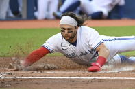 Toronto Blue Jays' Bo Bichette scores on a two-run double by Corey Dickerson during the first inning of a baseball game against the Cleveland Indians on Wednesday, Aug. 4, 2021, in Toronto. (Jon Blacker/The Canadian Press via AP)