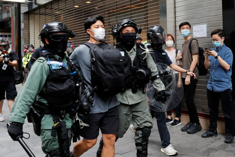 Riot police officers detain a demonstrator during a protest against the second reading of a controversial national anthem law in Hong Kong