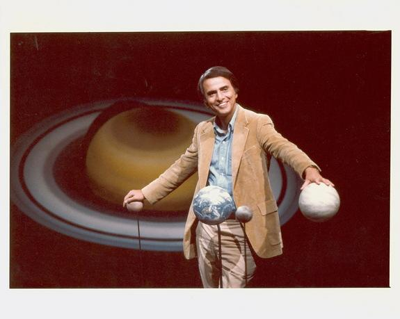 Carl Sagan standing with hands on globes of planets. Undated file photo.