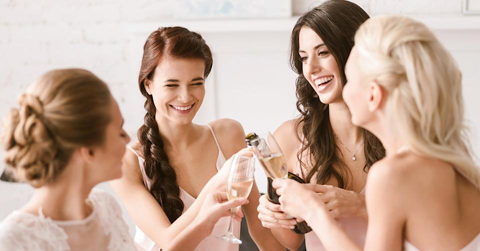 A bridal party clinking glasses