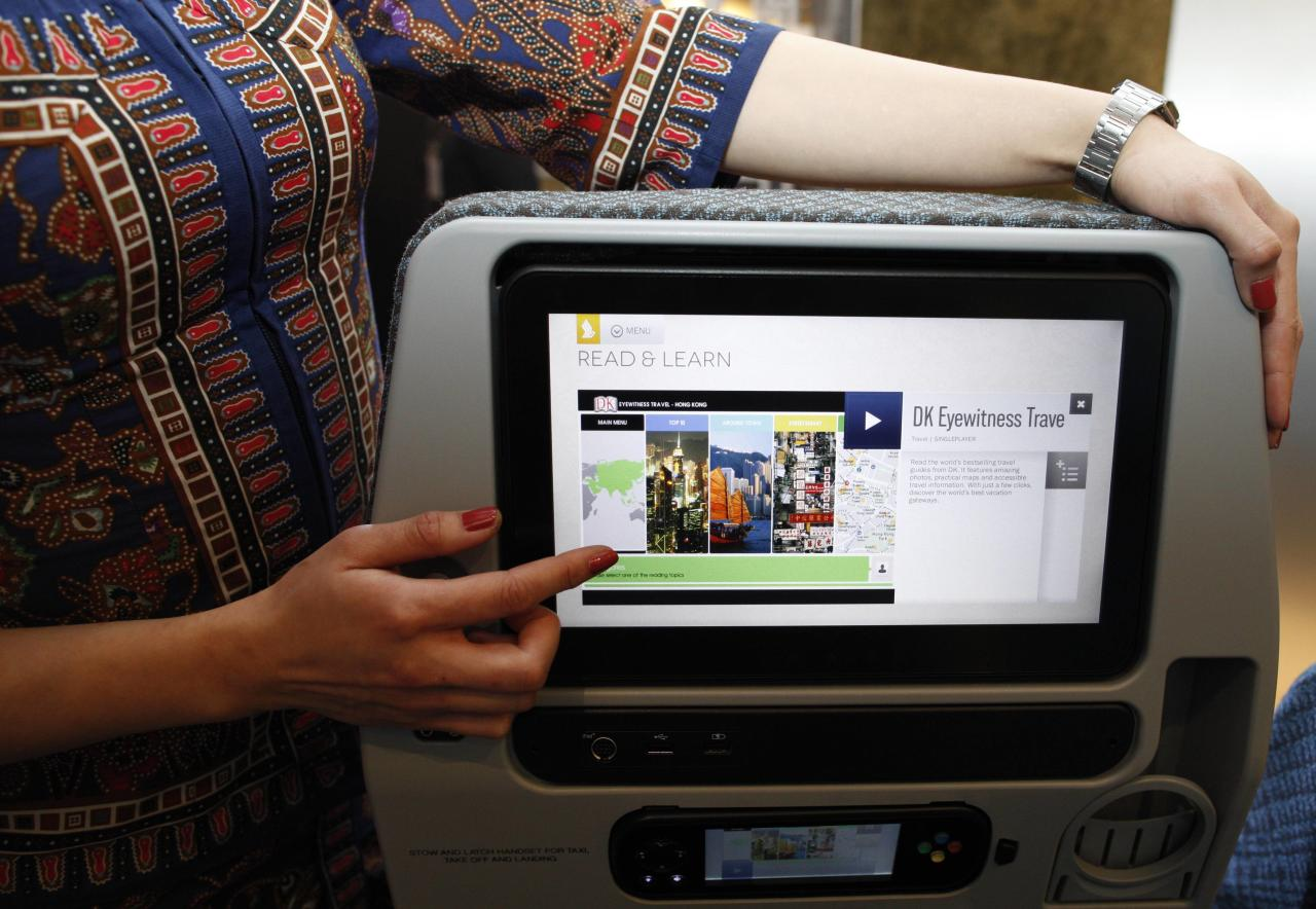 A Singapore Airlines Ltd stewardess poses with a new wider 11.1 inch monitor of the economy cabin during the launch of their new generation of cabin products at Changi Airport in Singapore July 9, 2013. The new seats and in-flight entertainment system, an investment of nearly $150 million by the company, will be rolled out from September, starting with flights between Singapore and London on eight Boeing 777-300ER aircrafts. REUTERS/Edgar Su (SINGAPORE - Tags: TRANSPORT BUSINESS)