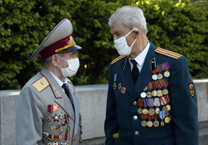 Two Soviet army veterans wearing face masks to protect against coronavirus talk to each other at a memorial to World War II veterans in a memorial park in Kyiv, Ukraine, Saturday, May 9, 2020 on the 75th anniversary of the end of World War II. Ukraine marks the 75th anniversary of the end of World War II in Europe at a time of coronavirus lockdown and loneliness spent in search of memories both bitter and sweet. (AP Photo/Efrem Lukatsky)