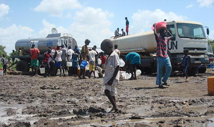 This handout photo provided by the United Nations Mission in the Republic of South Sudan (UNMISS) and released on July 16, 2016 shows a child crossing through mud as people receive rations of water at the UN compound in the Tomping area in Juba (AFP Photo/Beatrice Mategwa)