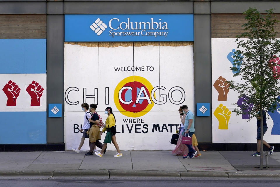 Shoppers walk past Black Lives Matter murals on the boarded up windows and doors of a Columbia clothing store on Chicago's Magnificent Mile on Tuesday, Aug. 11, 2019. (AP Photo/Charles Rex Arbogast)