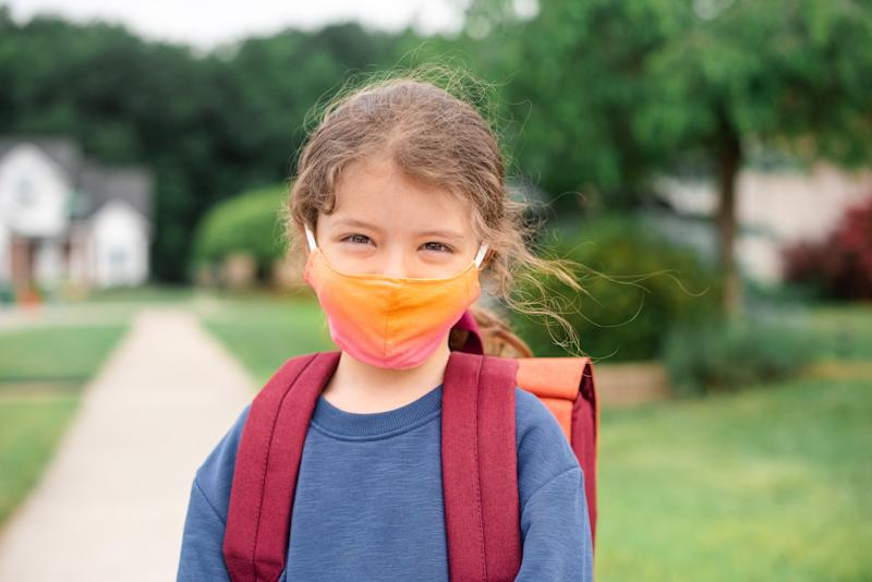Caucasian little girl ready to go to school wearing a face mask