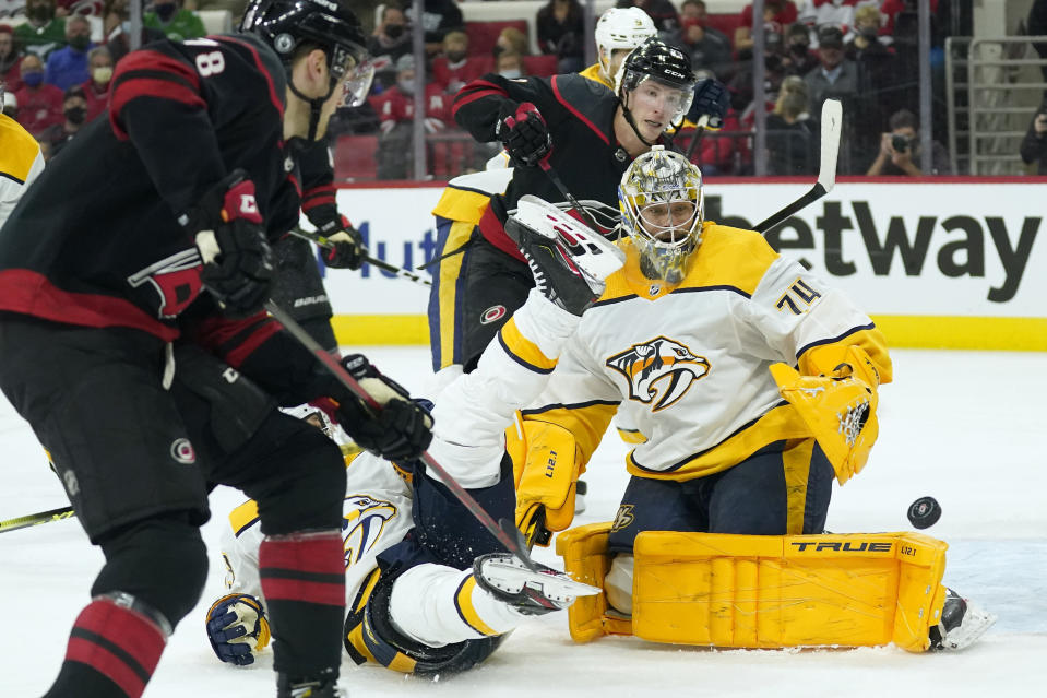 Nashville Predators goaltender Juuse Saros (74) keeps an eye on the puck as Carolina Hurricanes left wing Steven Lorentz (78) and left wing Brock McGinn (23) try to get a shot during the second period in Game 1 of an NHL hockey Stanley Cup first-round playoff series in Raleigh, N.C., Monday, May 17, 2021. (AP Photo/Gerry Broome)