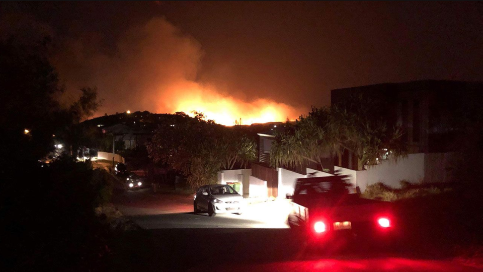 Queensland bushfire photo of houses in the foreground of massive flames.