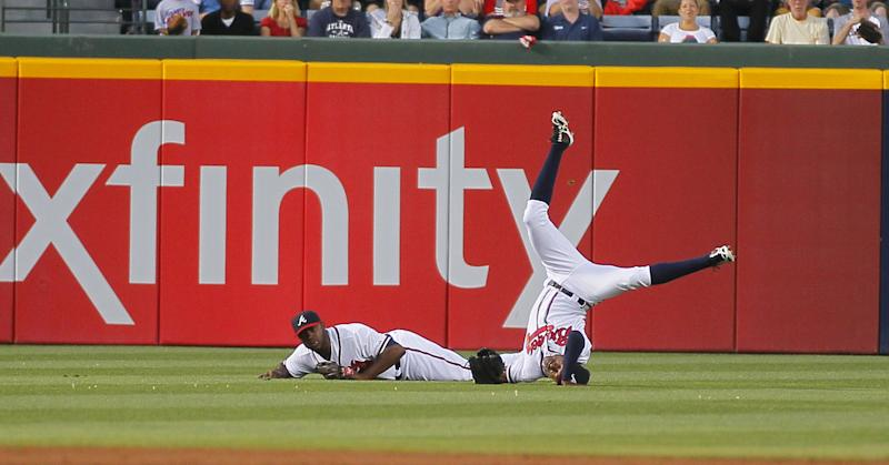 Atlanta Braves center fielder B.J. Upton, right, and left fielder Justin Upton, left, collide in the outfield catching the ball to end the fourth inning in the second baseball game of the doubleheader against the New York Mets Tuesday, June 18, 2013, in Atlanta. (AP Photo/Todd Kirkland)