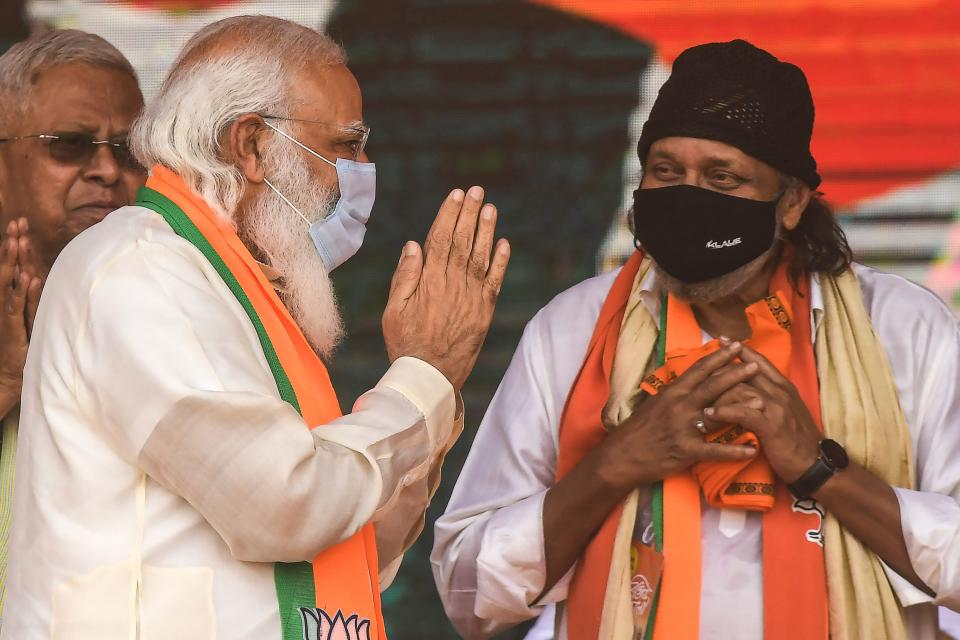 Bollywood actor Mithun Chakraborty (L), a former Trinamool Rajya Sabha member, greets India's Prime Minster Narendra Modi during a mass rally ahead of the state legislative assembly elections at the Brigade Parade ground in Kolkata on March 7, 2021. (Photo by Dibyangshu SARKAR / AFP) (Photo by DIBYANGSHU SARKAR/AFP via Getty Images)