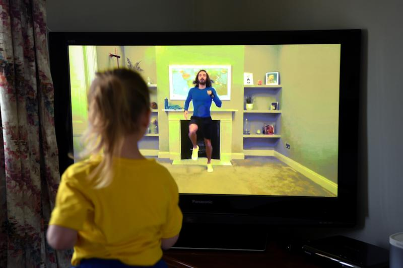 Four-year-old Lois Copley-Jones, who is the photographer's daughter, takes part in a live streamed broadcast of PE with fitness trainer Joe Wicks on the first day of the nationwide school closures on March 23, 2020 in Newcastle Under Lyme, United Kingdom. (Photo by Gareth Copley/Gareth Copley)