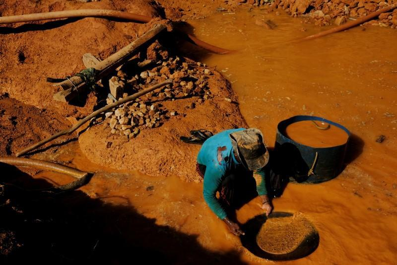 FILE PHOTO: A wildcat gold miner, or garimpeiro, uses a basin and mercury to pan for gold at a wildcat gold mine, also known as a garimpo, at a deforested area of the Amazon rainforest near Crepurizao, in the municipality of Itaituba