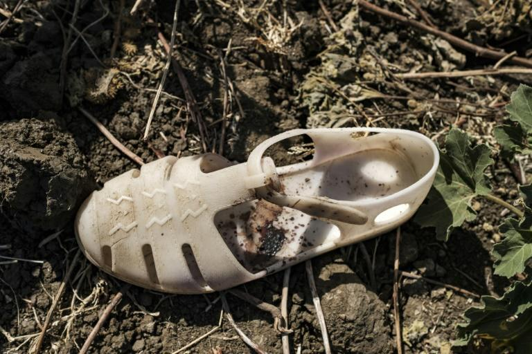 A blood-stained sandal lies next to the grave of an alleged victim of a massacre that unfolded in the Tigrayan town of Mai Kadra November 9, 2020
