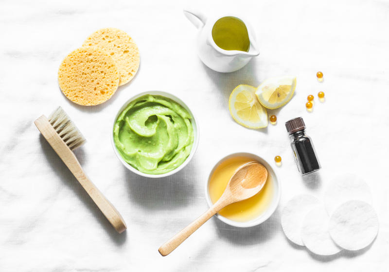 Honey and avocado face mask on light background, top view. Beauty, youth, skin care concept. Flat lay