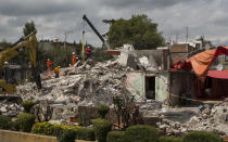 <p>Specialists and soldiers search for survivors at a building felled by a 7.1-magnitude earthquake in San Gregorio Atlapulco, Mexico, Friday, Sept. 22, 2017. Mexican officials are promising to keep up the search for survivors as rescue operations stretch into a fourth day following Tuesday's major earthquake that devastated Mexico City and nearby states. (AP Photo/Moises Castillo) </p>